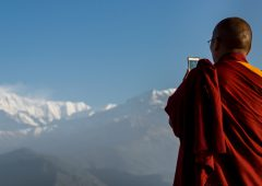 Pokhara, Kaski District, Nepal - April 4, 2015: Buddhist monk with a mobile phone taking pictures of Annapurna range, Phokara, Nepal